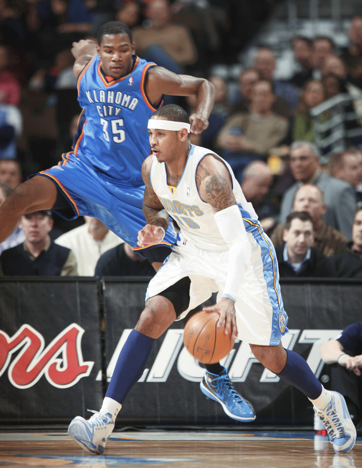 Denver's Carmelo Anthony, right, drives past OKC's Kevin Durant during action on Monday. AP photo