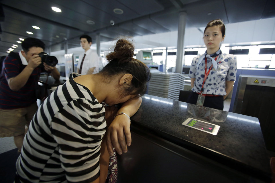 Photo - An unidentified family member of one of two Chinese students killed in a crash of an Asiana Airlines' plane on Saturday, cries at the airline's counter as she and other family members check in for a flight to San Francisco, at Pudong International Airport in Shanghai, China, Monday, July 8, 2013. The Asiana flight crashed upon landing Saturday, at San Francisco International Airport, and two of the 307 passengers aboard were killed. (AP Photo/Eugene Hoshiko)