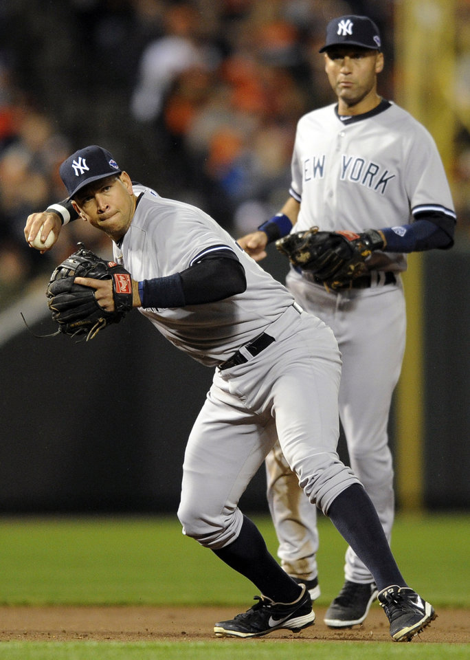 New York Yankees third baseman Alex Rodriguez, front, fields a ground ball by Baltimore Orioles\' Matt Wieters in front of shortstop Derek Jeter in the second inning of Game 2 of the American League division baseball series on Monday, Oct. 8, 2012, in Baltimore. (AP Photo/Nick Wass)