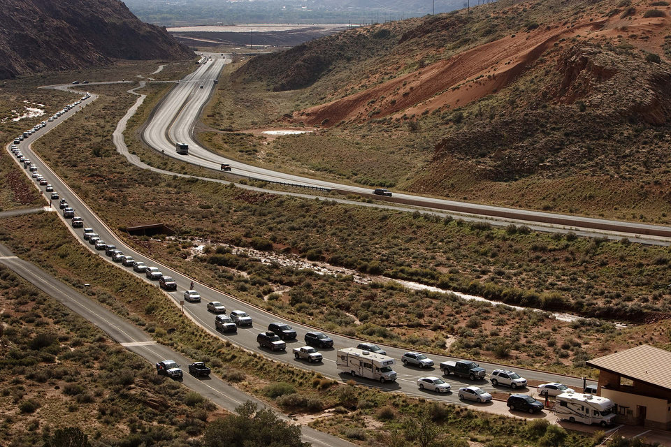 Photo - Vehicles wait at the entrance to Arches National Park, Saturday, Oct. 12, 2014.  Thanks to a $1.7 million payment from Utah taxpayers, the national parks of southern Utah are being exempted from the federal government shutdown just in time for a traditionally busy fall weekend.  AP Photo/The Salt Lake Tribune, Leah Hogsten)  DESERET NEWS OUT; LOCAL TV OUT; MAGS OUT