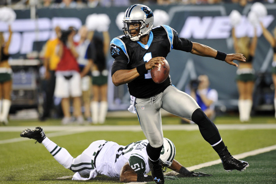 Photo -   Carolina Panthers quarterback Cam Newton (1) avoids a tackle by New York Jets linebacker Aaron Maybin (51) during the first half of a preseason NFL football game, Sunday, Aug. 26, 2012, in East Rutherford, N.J. (AP Photo/Bill Kostroun)