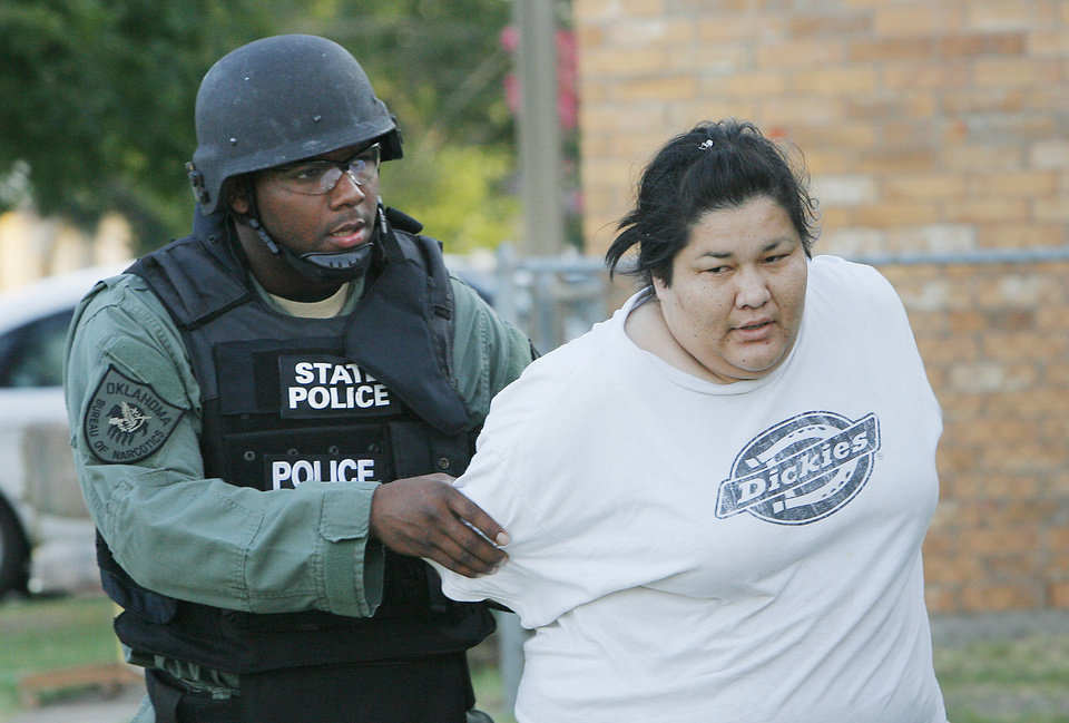 Photo - An Oklahoma Bureau of Narcotics agent takes an unidentified woman into custody during a meth raid. Oklahoma Bureau of Narcotics executed a large-scale raid Tuesday morning, July 14, 2009, in Caddo County, launching out of Anadarko,   Photo By David McDaniel, The Oklahoman.