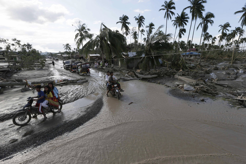 Residents make their way through a flooded area of New Bataan township, Compostela Valley in southern Philippines Wednesday, Dec. 5, 2012, a day after Typhoon Bopha made landfall. Typhoon Bopha, one of the strongest typhoons to hit the Philippines this year, barreled across the country's south on Tuesday, killing scores of people while triggering landslides, flooding and cutting off power in two entire provinces. (AP Photo/Bullit Marquez)