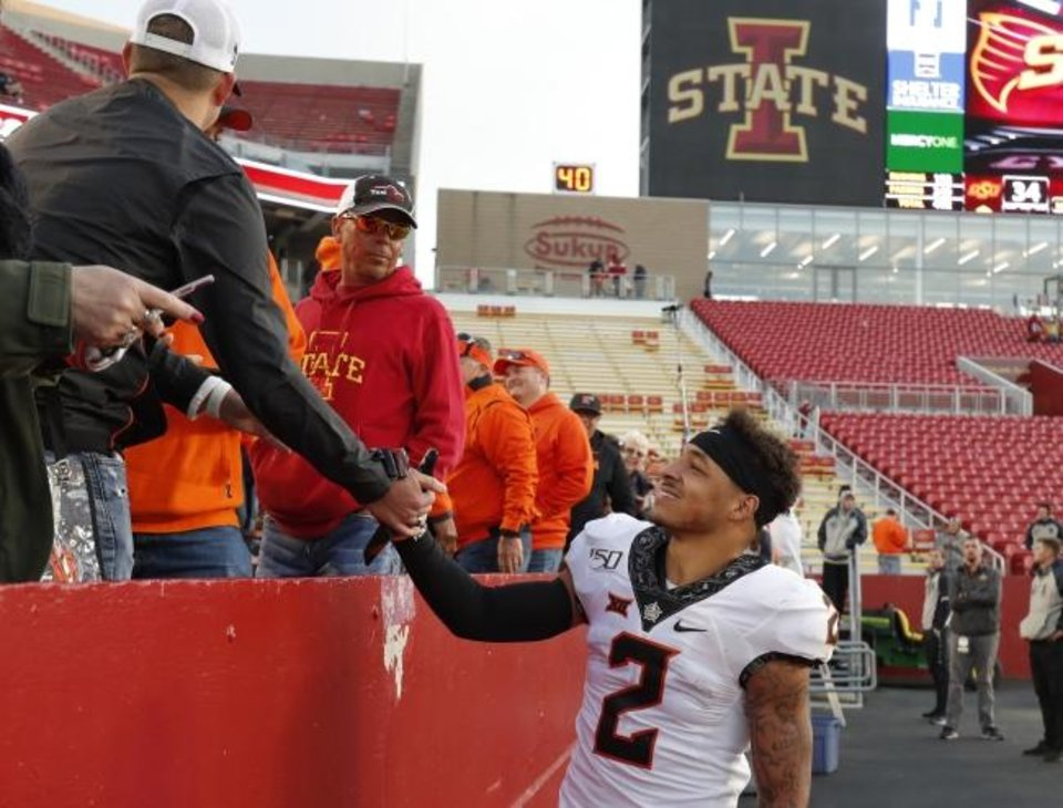Photo -  Oklahoma State wide receiver Tylan Wallace, right, celebrates Oklahoma State's 34-27 win over Iowa State with fans after their game Saturday in Ames, Iowa. [AP Photo/Matthew Putney]