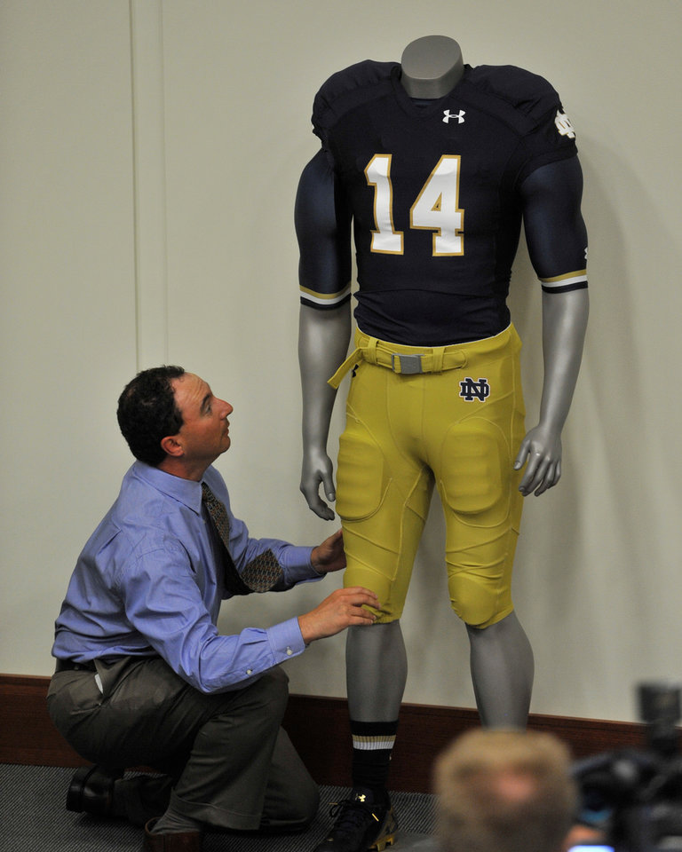 Photo - Notre Dame sports information representative Leigh Torbin sets up the new Notre Dame home team uniform during media day for the NCAA college football team Tuesday Aug. 19, 2014 in South Bend, Ind. (AP Photo/Joe Raymond)