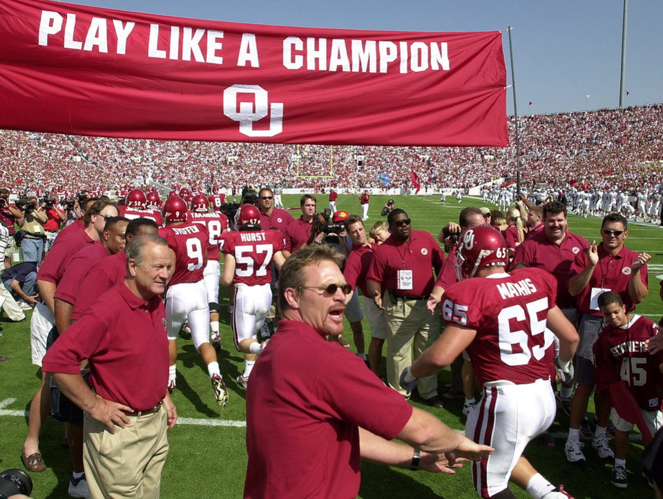 "Coach Barry Switzer, left, is joined by Brian Bosworth, foreground, and other players from OU's 1985 national championship team on the field before Saturday's game against Rice.  The players were introduced prior to the start of the game and they formed a ""human tunnel"" for this year's team to run through as they took the field. Photo from The Oklahoman Archives."