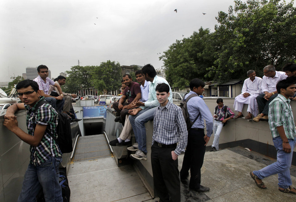Photo -   Commuters wait outside a Metro station after Delhi Metro rail services were disrupted following power outage in New Delhi, India, Tuesday, July 31, 2012. India's energy crisis cascaded over half the country Tuesday when three of its regional grids collapsed, leaving more than 600 million people without government-supplied electricity in one of the world's biggest-ever blackouts.(AP Photo/ Manish Swarup)