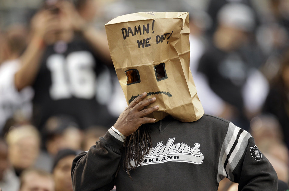 An Oakland Raiders wears a bag over his head during the fourth quarter of an NFL football game against the New Orleans Saints in Oakland, Calif., Sunday, Nov. 18, 2012. (AP Photo/Ben Margot)