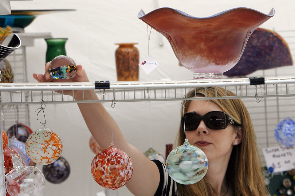 Photo - Jennifer Shoop, from Edmond, looks over some glass art at the Downtown Edmond Arts Festival, Friday, May 1, 2009.   Photo By David McDaniel, The Oklahoman