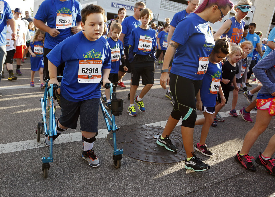Photo - Luke Stafford, 7, uses his walker as he takes part in the kid's marathon during the Oklahoma Memorial Marathon in Oklahoma City, Okla. on Sunday, April 24, 2016. Stafford suffers from Cerebral Palsy, and is his second year to finish the 1.2 mile kid's marathon.  Photo by Chris Landsberger, The Oklahoman