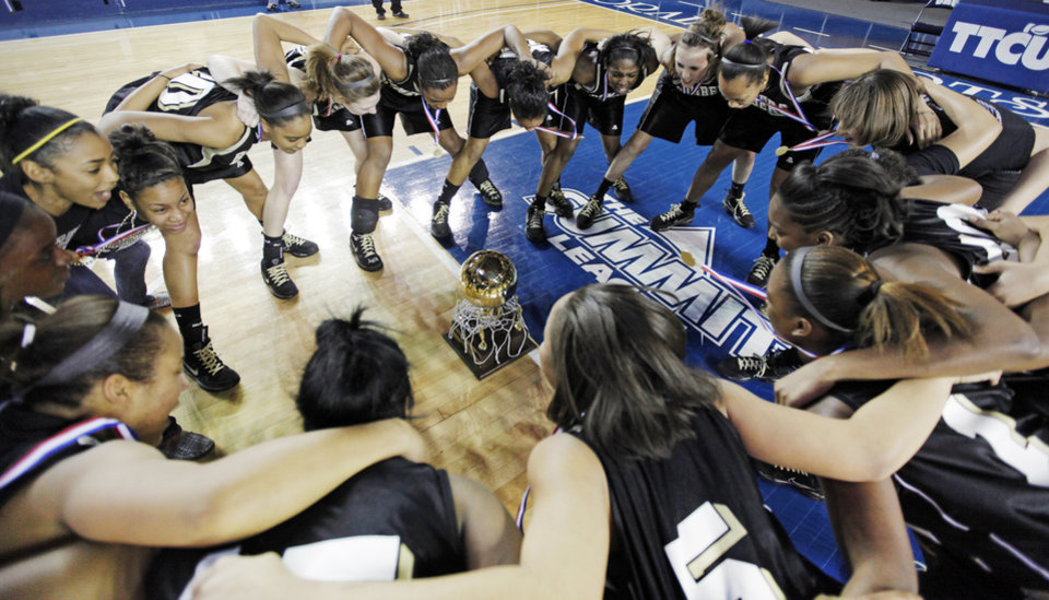 Photo - The Midwest City Lady Bombers cheer together around the gold ball championship trophy after the Class 6A girls high school basketball state tournament final between Midwest City and Norman at the ORU Mabee Center in Tulsa, Okla., Saturday, March 13, 2010. Midwest City won, 46-32. Photo by Nate Billings, The Oklahoman