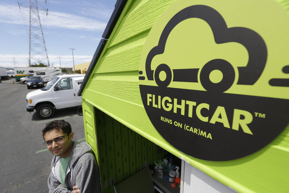 In this photo taken Tuesday, June 11, 2013 Flightcar CEO Rujul Zaparde, poses outside a small rental shack on their lot in Burlingame, Calif. A San Francisco Bay area startup company founded by three teenage Ivy League dropouts is trying to change the airport car rental business. FlightCar rents out people's personal vehicles while they are traveling, giving them a share of the proceeds and free airport parking in exchange. But the company's rosy outlook does have some thorns. San Francisco's City Attorney has sued FlightCar, accusing it of unfair competition. (AP Photo/Eric Risberg)