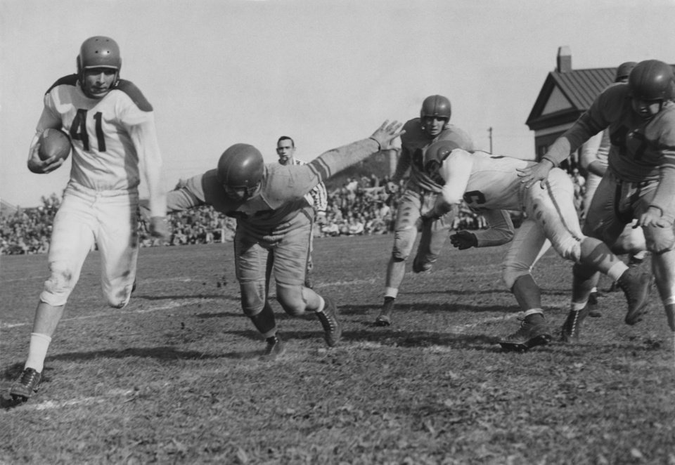 """Photo - Bob Riddle, former Frederick player, carries the ball for the 45th team, picking up 11 yards.  U.S. 45th Infantry Division, Hokkaido, Japan--(By Mail)--The vast Pacific ocean separates an army division of men from the land and the people they love best.  But the thousands of distant miles has not arrested the craving in men of the 45th Infantry division for things American.  A football game at Camp Crawford recently attracted the largest Thunderbird attendance for any single recreational event  since the Oklahoma National Guard was called to active duty more than a year ago.  While sleek automobiles zipped over ribbons of concrete leading to Owen stadium in Norman, olive drab trucks hauled OD dressed Thunderbirds over the bumpy, gravel road from Chitose to Camp Crawford.  Special trains and buses also hauled holiday-spirited 45th men in their too-small seats.  The T-Birds' first game, against Headquarters and Service command of GHQ in Tokyo, was an attraction all over Hokkaido.  Sailors, airforce men, marines and civilians trickled in from station on various parts of the island.  Toshibumi Tanaka, governor of Hokkaido, and a party of official dignitaries attended the game as guests of Maj. Gen. James C. Styron, division commander.  It was the first time for any of them to see American football.""""  Photo by Jack Gunter.  Original undated.  Published in The Daily Oklahoman 10/14/1951 [E]."""