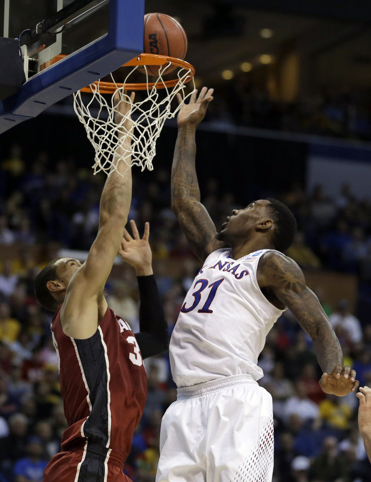 Photo - Kansas' Jamari Traylor, right, heads to the basket as Stanford's Dwight Powell defends during the first half of a third-round game of the NCAA college basketball tournament Sunday, March 23, 2014, in St. Louis. (AP Photo/Jeff Roberson)