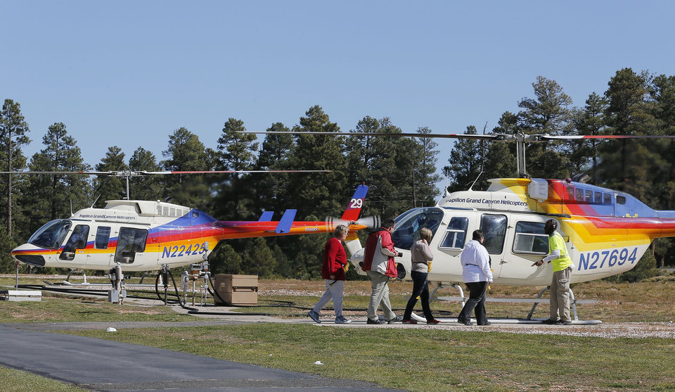 Photo - In this Oct. 11, 2013 photo, tourists prepare to get on a helicopter prior to taking a tour of the Grand Canyon, at Grand Canyon National Park Airport in Tusayan, Ariz. Air tour operators that use aircraft with quiet technology will be able to fly more people over the Grand Canyon. The Federal Aviation Administration said it plans to release 1,721 flight allocations this year that had been abandoned to those commercial tour operators, as long as their active fleet doesn't increase noise in the park overall. (AP Photo/Ross D. Franklin)
