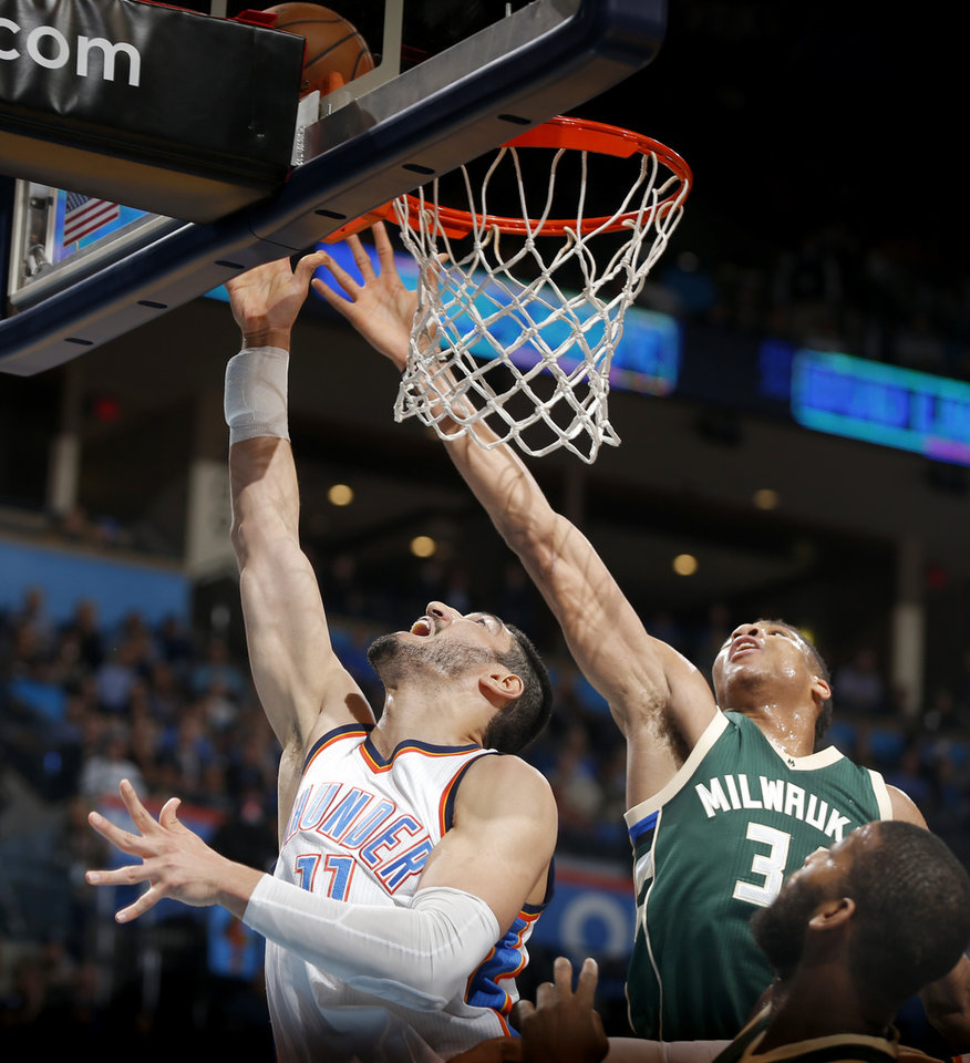 Photo - Oklahoma City's Enes Kanter (11) goes to the basket past Milwaukee's Giannis Antetokounmpo (34) during an NBA basketball game between the Oklahoma City Thunder and the Milwaukee Bucks at Chesapeake Energy Arena in Oklahoma City, Tuesday, April 4, 2017. Photo by Bryan Terry, The Oklahoman