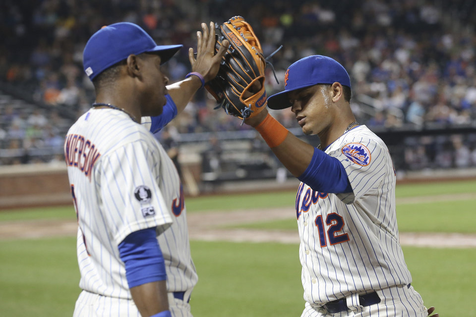 Photo - New York Mets' Juan Lagares (12) and Curtis Granderson high-five in the ninth inning of a baseball game against the Atlanta Braves, Wednesday, Aug. 27, 2014, in New York. The Braves won 3-2. (AP Photo/John Minchillo)