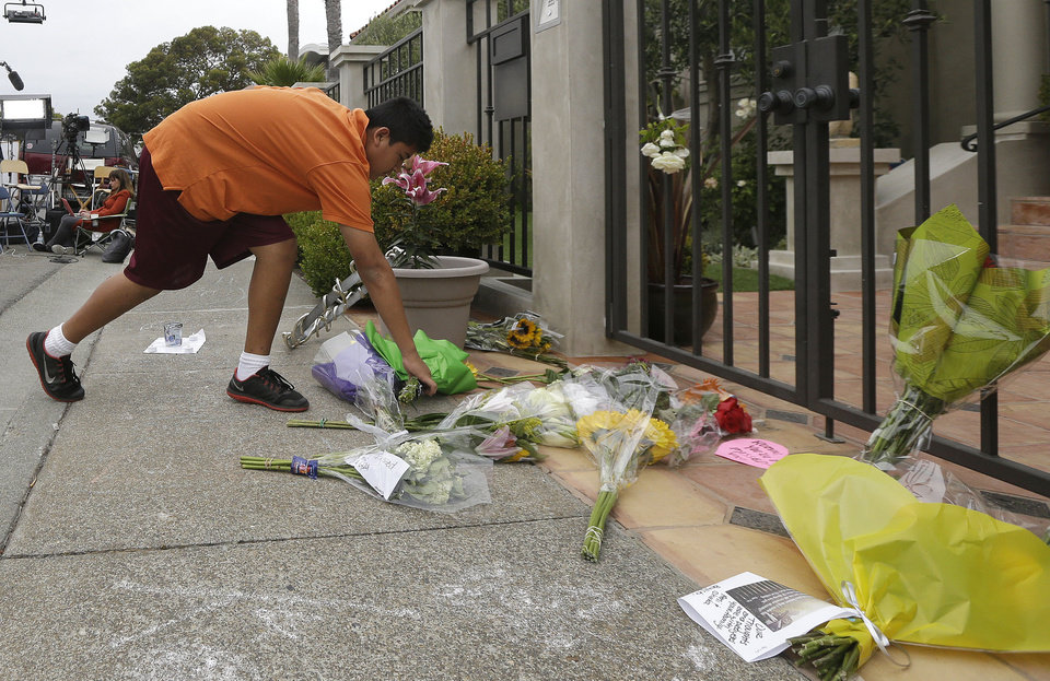 Photo - Brandon Antonio, 13, of San Rafael, leaves flowers outside of the home of Robin Williams in Tiburon, Calif., Tuesday, Aug. 12, 2014. Williams died Monday in an apparent suicide at his San Francisco Bay Area home, according to the sheriff's office in Marin County, north of San Francisco. (AP Photo/Jeff Chiu)