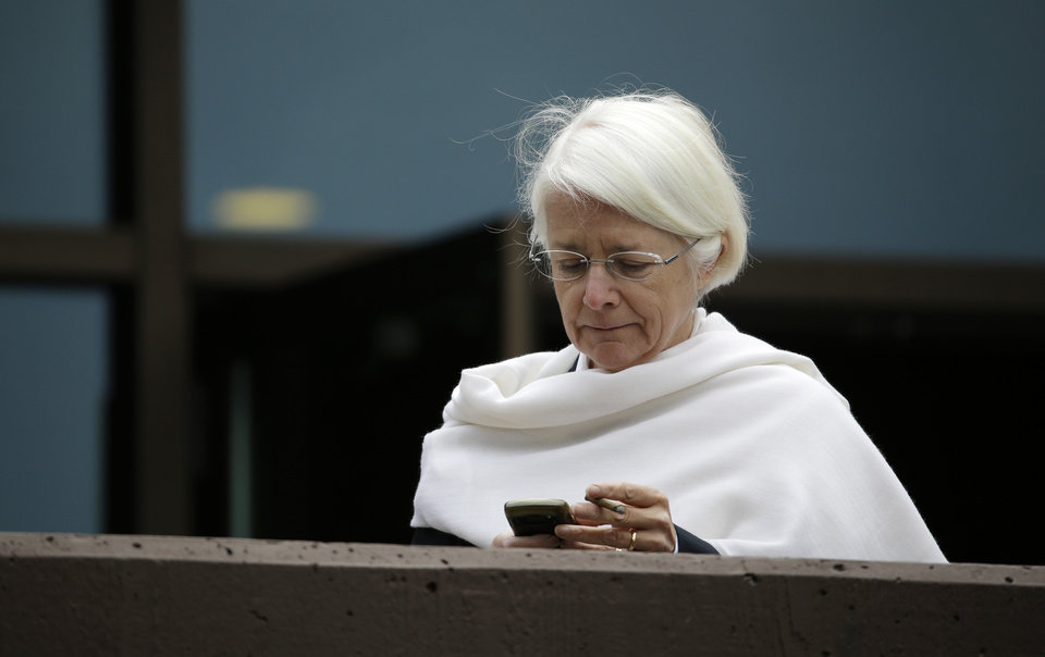Photo - Anne Le Lorier, Banque de France deputy governor, looks at her phone during a break at the Jackson Hole Economic Policy Symposium at the Jackson Lake Lodge in Grand Teton National Park near Jackson, Wyo. Saturday, Aug. 23, 2014. (AP Photo/John Locher)