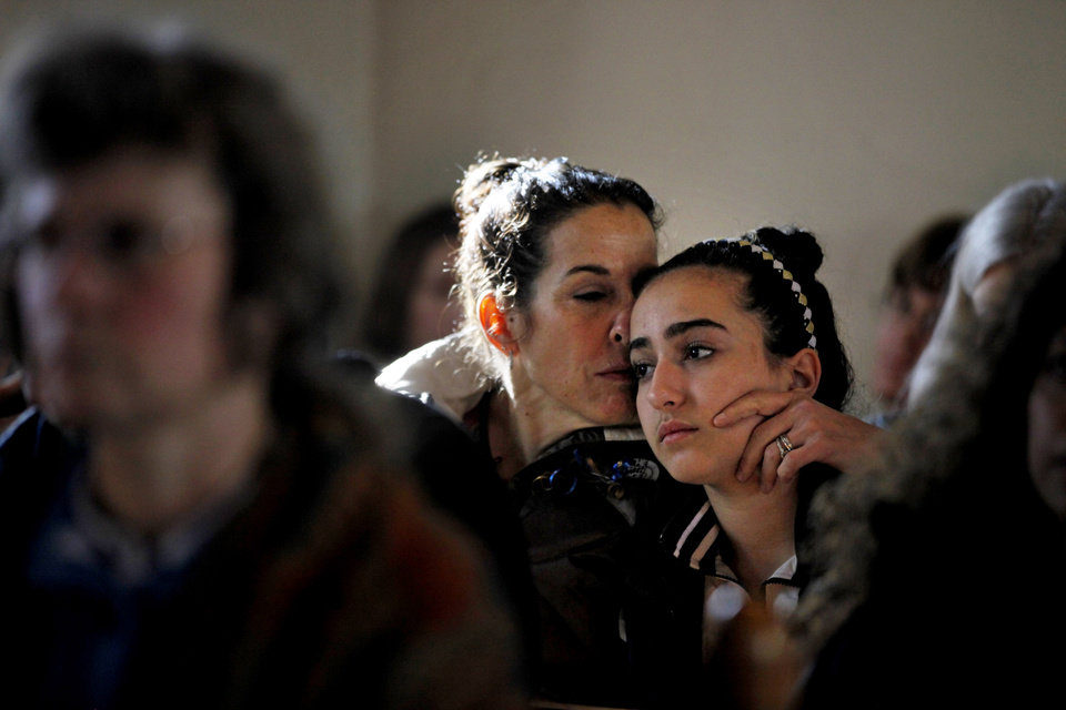 Photo - Elizabeth Bogdanoff, left, kisses her daughter Julia, 13, both of Newtown, Conn., during a prayer service at St John's Episcopal Church in Newtown, Saturday, Dec. 15, 2012. The massacre of 26 children and adults at Sandy Hook Elementary school elicited horror and soul-searching around the world even as it raised more basic questions about why the gunman, 20-year-old Adam Lanza, would have been driven to such a crime and how he chose his victims. (AP Photo/David Goldman) ORG XMIT: CTDG114