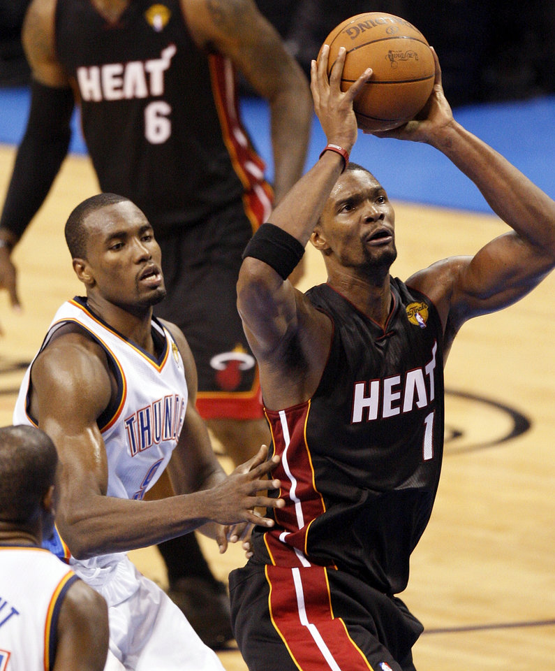 Miami's Chris Bosh (1) takes the ball to the hoop past Oklahoma City's Serge Ibaka (9) during Game 2 of the NBA Finals between the Oklahoma City Thunder and the Miami Heat at Chesapeake Energy Arena in Oklahoma City, Thursday, June 14, 2012. Photo by Nate Billings, The Oklahoman