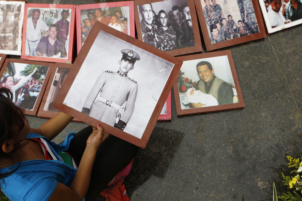 Photo - A mourner places a photo of the late President Hugo Chavez when he was a military cadet on a makeshift altar at the main square of Sabaneta, the town of his birth in western Venezuela on Saturday, March 9, 2013. Chavez died of cancer on March 5, 2013. His former house has been turned into the local headquarters of the United Socialist Party of Venezuela, PSUV. (AP Photo/Esteban Felix)