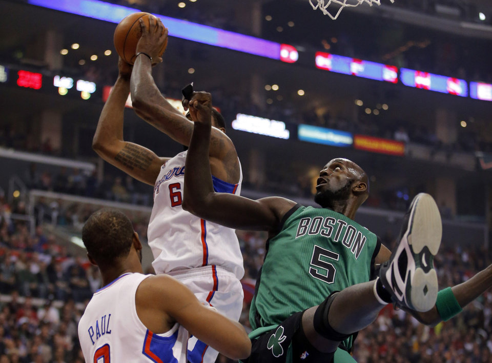 Los Angeles Clippers\' DeAndre Jordan, top left, grabs a rebound against Boston Celtics\' Kevin Garnett in the first half of an NBA basketball game in Los Angeles, Thursday, Dec. 27, 2012. (AP Photo/Jae C. Hong)
