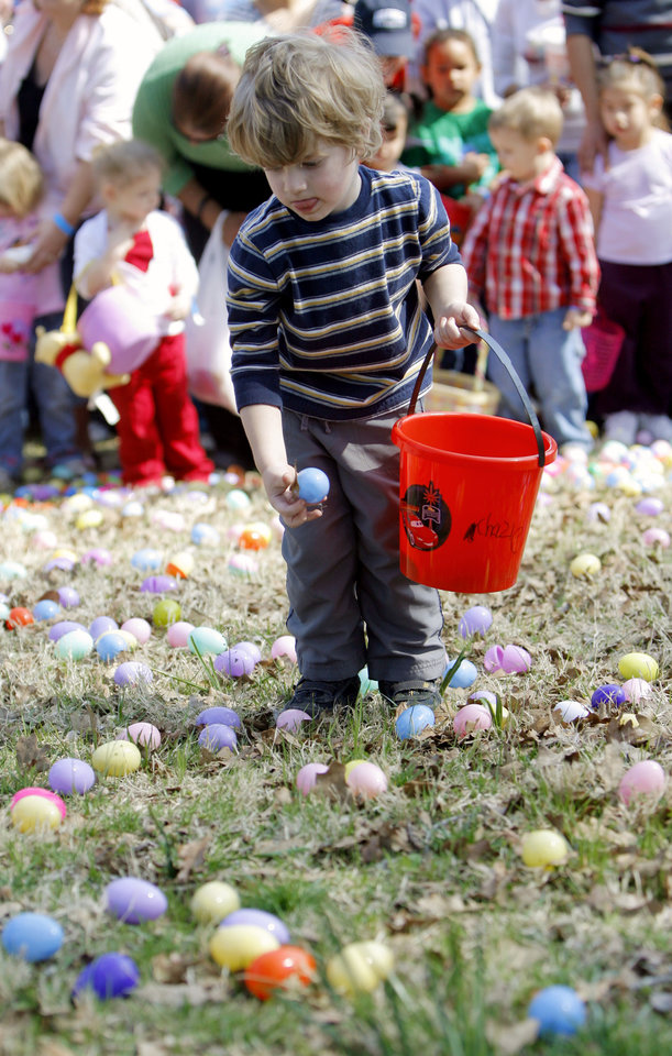 Photo - A child hunts easter eggs before the start of the Cathedral of the Hills Easter egg hunt at Hafer Park in Edmond, Okla., Saturday, March 22, 2008. BY MATT STRASEN, THE OKLAHOMAN