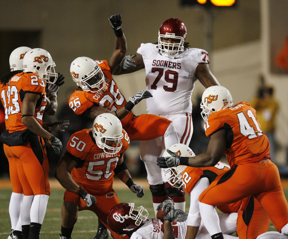 Cowboy defense celebrates a stop of Chis Brown during the first half of the college football game between the University of Oklahoma Sooners (OU) and Oklahoma State University Cowboys (OSU) at Boone Pickens Stadium on Saturday, Nov. 29, 2008, in Stillwater, Okla. STAFF PHOTO BY SARAH PHIPPS
