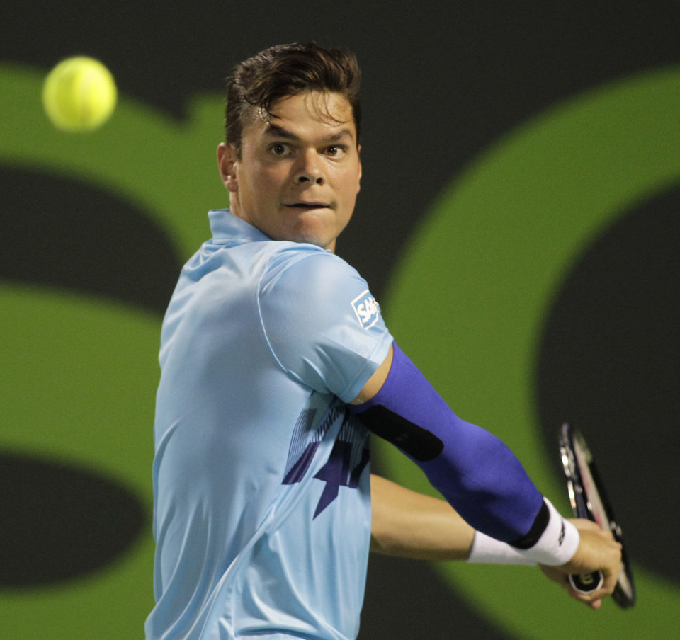 Photo - Milos Raonic, of Canada, returns the ball to Rafael Nadal, of Spain, during the Sony Open tennis tournament, Thursday, March 27, 2014, in Key Biscayne, Fla. (AP Photo/Luis M. Alvarez)