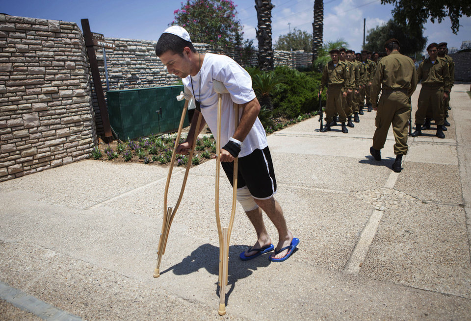 Photo - A wounded Israeli soldier arrives for the funeral of Maj. Tzafrir Bar-Or, 32, one of 13 soldiers killed in several separate incidents in Shijaiyah on Sunday, at the military cemetery in Holon, Israel, Monday, July 21, 2014. On Sunday, the first major ground battle in two weeks of Israel-Hamas fighting exacted a steep price, killing scores of Palestinians and more than a dozen Israeli soldiers and forcing thousands of terrified Palestinian civilians to flee their devastated Shijaiyah neighborhood, which Israel says is a major source for rocket fire against its civilians. (AP Photo/Dan Balilty)