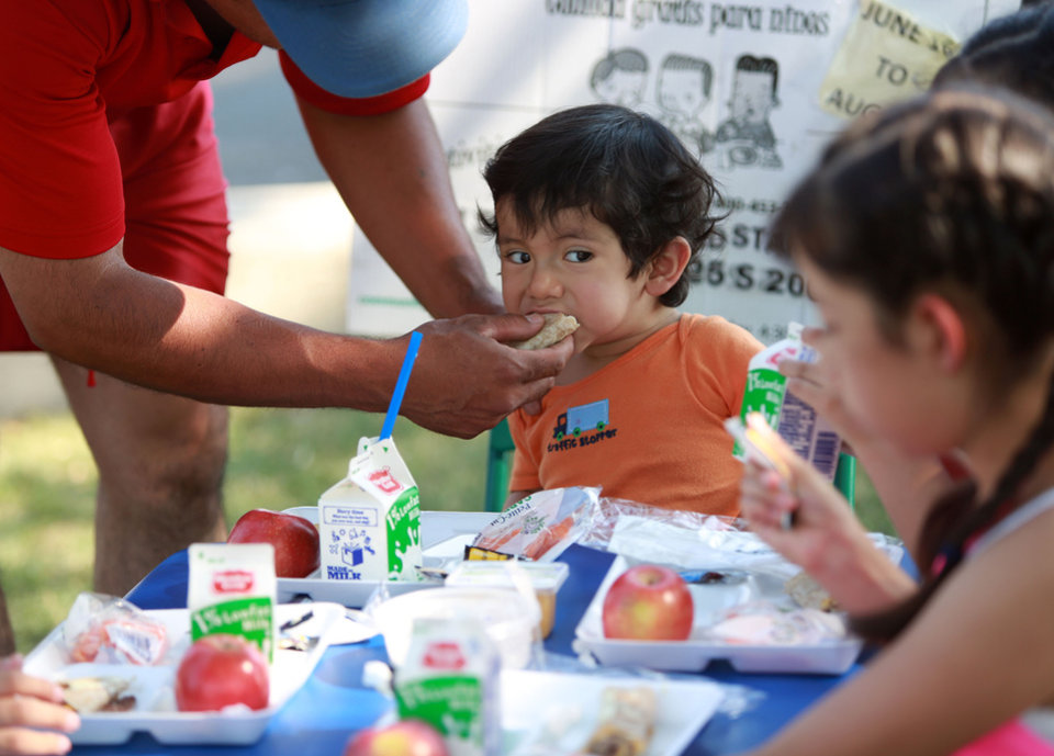 Photo -       Patrick Perez feeds his son Emanuel Perez outside of the Central Park Community Center in South Salt Lake on Friday, July 18, 2014. The dinner is part of the Salt Lake CAP summer food program, which offers free dinner to children at five locations in the valley, Monday through Friday. The Perez family brought their own table and chairs for the children to eat on.