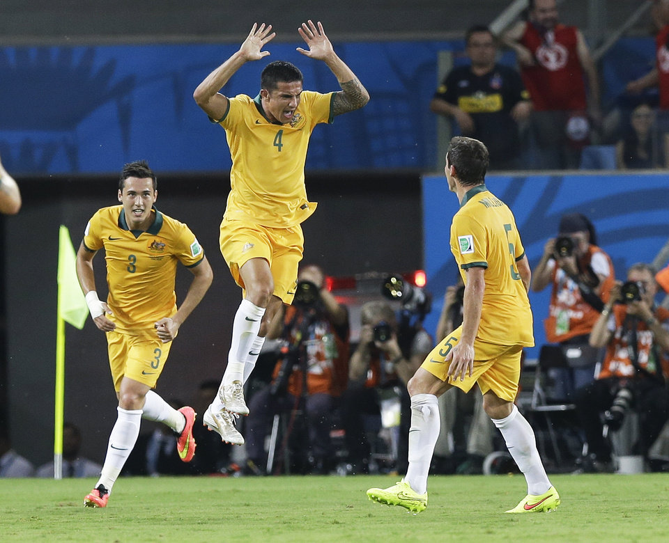 Photo - Australia's Tim Cahill (4) celebrates with Mark Milligan (5) and Jason Davidson (3) after Cahill scored his side's first goal during the first half of the group B World Cup soccer match between Chile and Australia in the Arena Pantanal in Cuiaba, Brazil, Friday, June 13, 2014. (AP Photo/Thanassis Stavrakis)