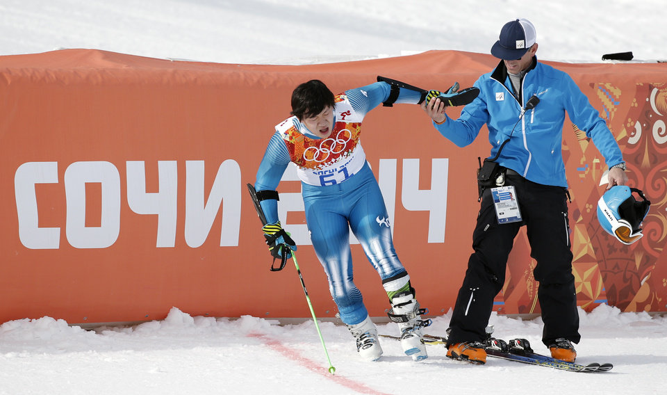 Photo - An official assists South Korea's Kyung Sung-yun after he crashed  in the first run of the men's giant slalom at the Sochi 2014 Winter Olympics, Wednesday, Feb. 19, 2014, in Krasnaya Polyana, Russia. (AP Photo/Christophe Ena)