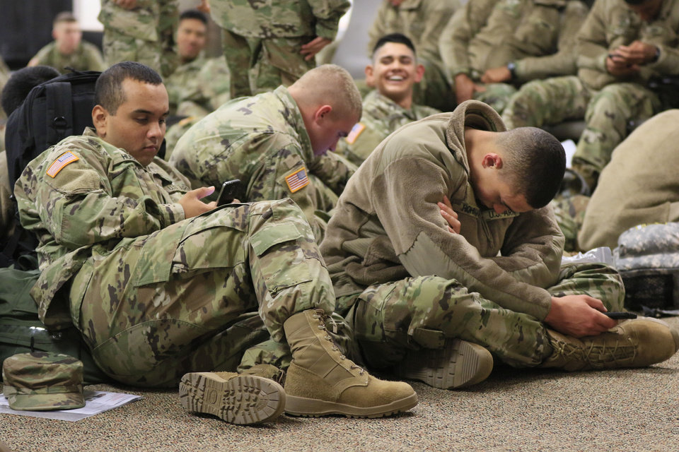 Photo - Jesus Huerta, from California, left, and Nate Hohman, from Colorado, pass the minutes on their smartphones, as soldiers from Ft. Sill gather at Will Rogers World Airport in Oklahoma City, Okla. on their way home for Christmas, Monday, Dec. 19, 2016.  Photo by Paul Hellstern, The Oklahoman