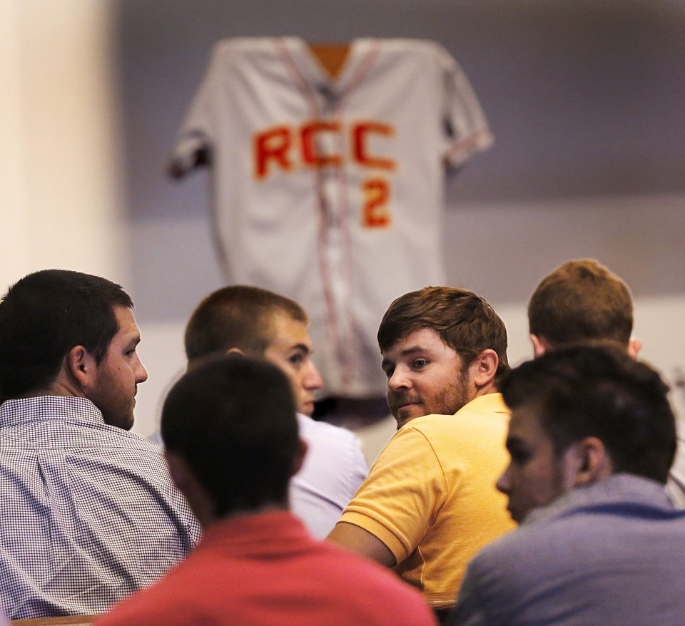 Photo - Baseball players from Redlands Community College in El Reno, Okla., fill the front benches at the memorial service. On the stage is a Redlands baseball jersey bearing the number Christopher Ryan Lane wore when he played there. About 200 friends, many of them former college baseball teammates,  attended a memorial service at Oklahoma Christian University  Saturday afternoon, Aug. 24, 2013, to remember student-athlete Christopher Lane during a memorial service for the East Central University athlete who was gunned down while jogging in Duncan, Okla. last week.   Photo  by Jim Beckel, The Oklahoman.
