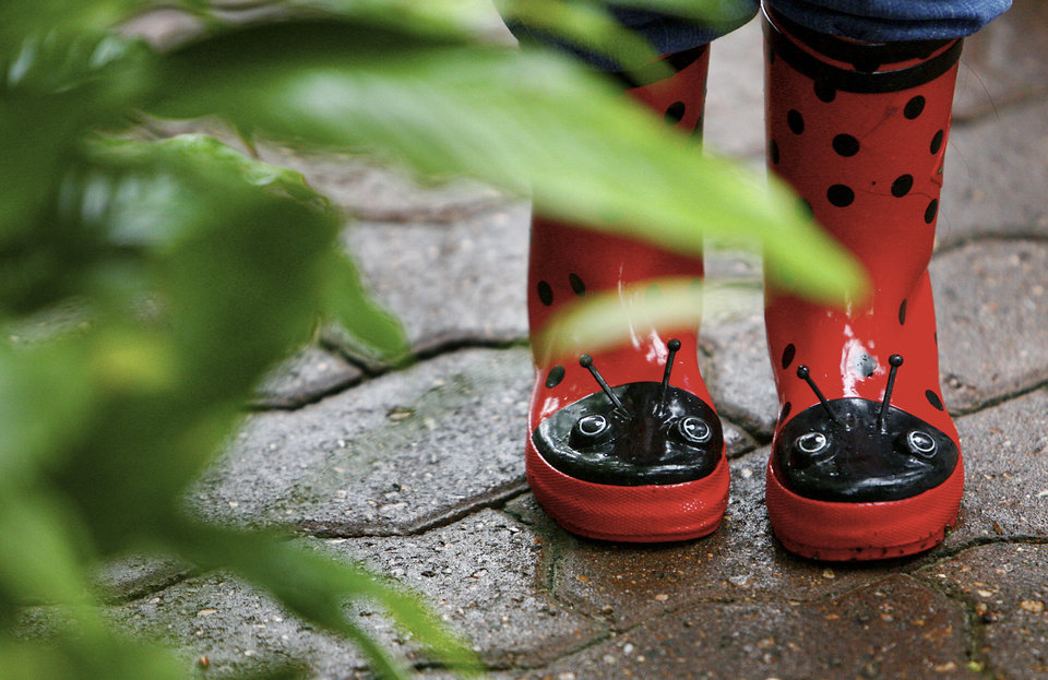 A pair of ladybug boots worn by Samantha Sears look as though they are peering from behind the foliage during the annual Crystal Bridge Bug Out at the Myriad Botanical Gardens Crystal Bridge on Tuesday, May 8, 2007, in Oklahoma City, Okla. More than 70,000 ladybugs were released into the garden to help with pest control in the facility.     staff photo by CHRIS LANDSBERGER ORG XMIT: KOD