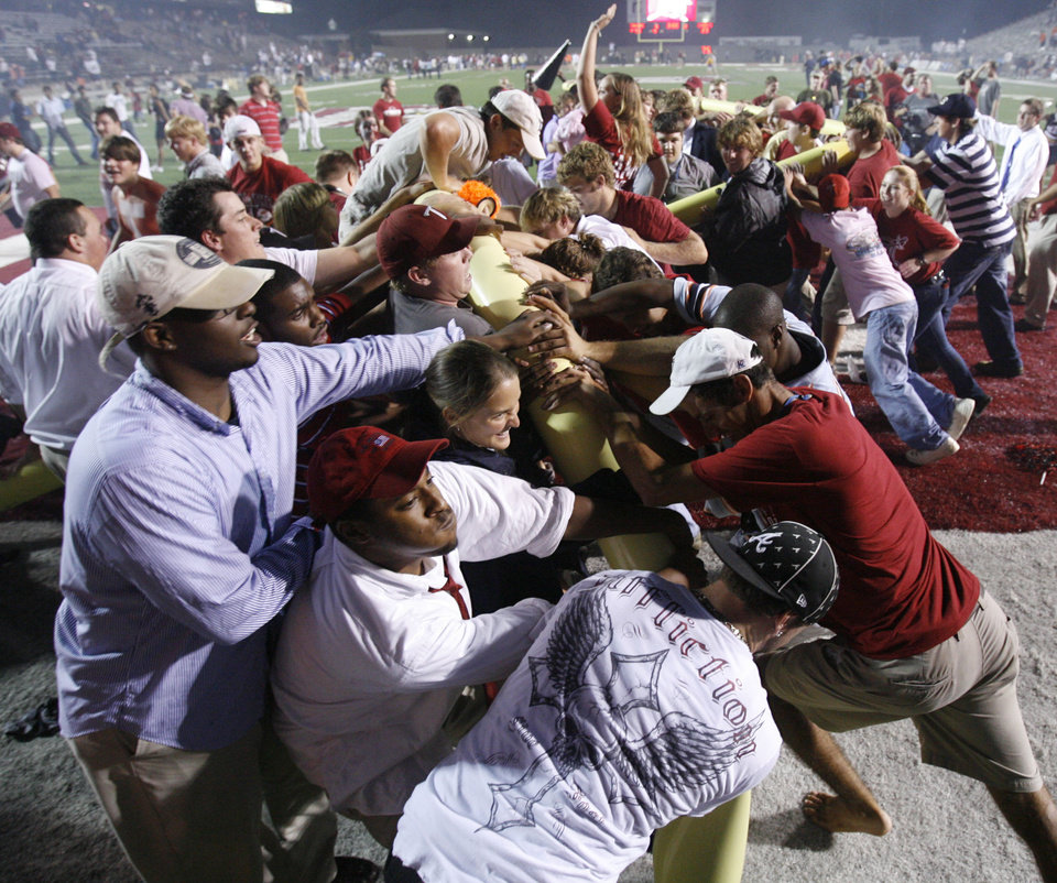 Photo - Troy Fans tear down the goal post after their 41-23 win in  college football game between the Troy University Trojans and the Oklahoma State University Cowboys at Movie Gallery Veterans Stadium in Troy, Ala., Friday, September 14, 2007. BY STEVE SISNEY, THE OKLAHOMAN