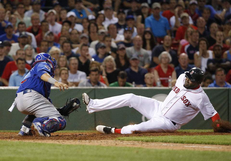 Photo - Chicago Cubs catcher Welington Castillo applies the tag as Boston Red Sox designated hitter David Ortiz is out trying to score on a fielder's choice grounder by Xander Bogaerts in the sixth inning of a baseball game at Fenway Park in Boston, Wednesday, July 2, 2014. (AP Photo/Elise Amendola)