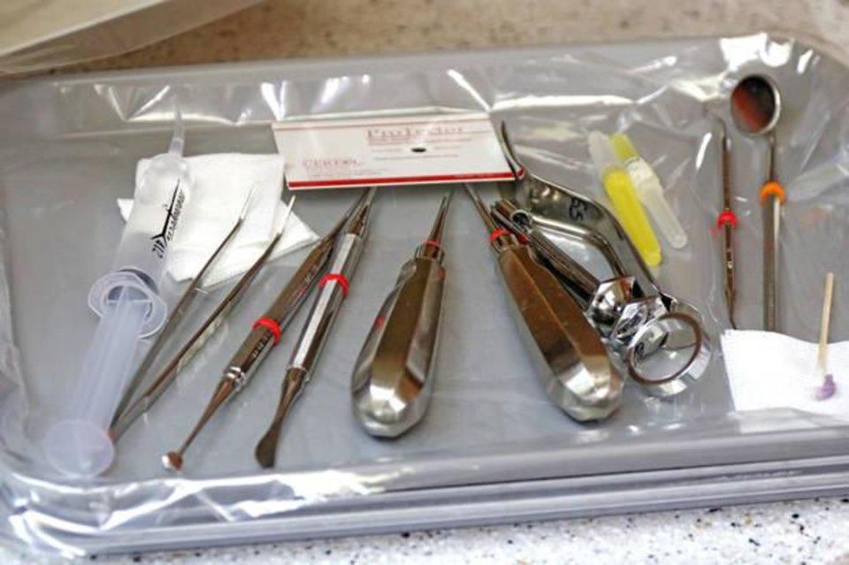 Photo -  Dental instruments are placed on a tray in preparation for a tooth extraction at the Good Shepherd clinic Monday. [Photo By Steve Gooch, The Oklahoman]