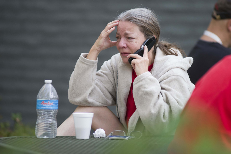 Photo - Nancy Myers is emotional as she speaks to her boss to let him know that she won't be able to make it into work due to the Yarnell Hill Fire on Monday, July 1, 2013, at the Red Cross Shelter in Prescott, Ariz.  The wildfire destroyed 200 houses in the town of Yarnell and the nearby community of Glen Isla. Nineteen firefighters from an elite crew from Prescott were killed in the blaze.    (AP Photo/The Arizona Republic, Aaron Lavinsky)  MARICOPA COUNTY OUT; MAGS OUT; NO SALES
