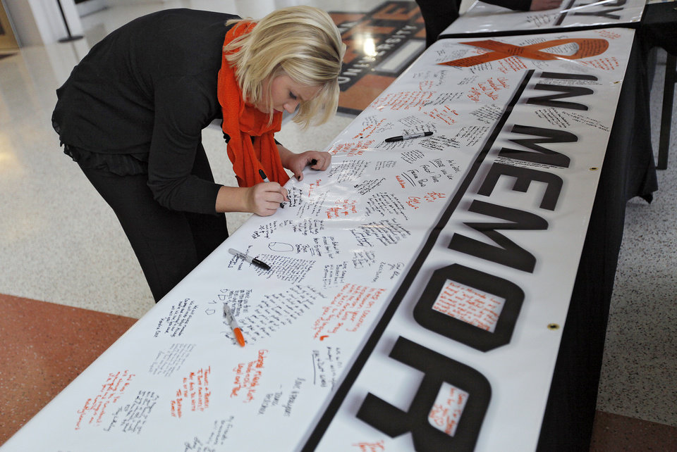 Photo - Caroline Bremer leave a message on the memorial banner during the memorial service for Oklahoma State head basketball coach Kurt Budke and assistant coach Miranda Serna at Gallagher-Iba Arena on Monday, Nov. 21, 2011 in Stillwater, Okla. The two were killed in a plane crash along with former state senator Olin Branstetter and his wife Paula while on a recruiting trip in central Arkansas last Thursday. Photo by Chris Landsberger, The Oklahoman