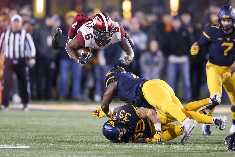 Photo - Oklahoma Sooners cornerback Tre Brown (6) flies through the air after being hit by West Virginia Mountaineers wide receiver Ricky Johns (36) during the NCAA football game between the Oklahoma Sooners and the West Virginia Mountaineers at Mountaineer Field at Milan Puskar Stadium in Morgantown, W.Va on Friday, November 23, 2018. IAN MAULE/Tulsa World