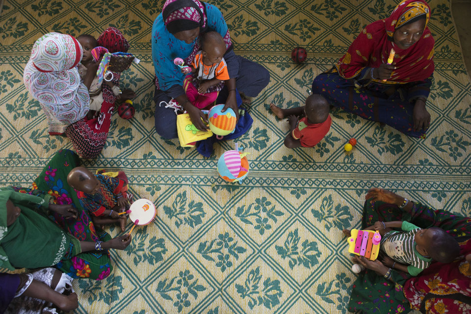Photo - ADVANCE FOR SATURDAY DEC 22, 2012 In this Nov. 5, 2012 photo, mothers try to engage their malnourished children in playtime as part of the treatment program at a nutritional health clinic run by Action Against Hunger with the support of UNICEF, in Moussoro, Chad. In this Sahel nation, childhood malnutrition and related mortality persist at alarming rates, despite the fact that many affected families live within a day's journey of internationally-funded nutrition clinics. One reason is that families, bound by local custom, choose instead to seek traditional treatments, treatments which can lead to the very infections that kill their undernourished children.(AP Photo/Rebecca Blackwell)