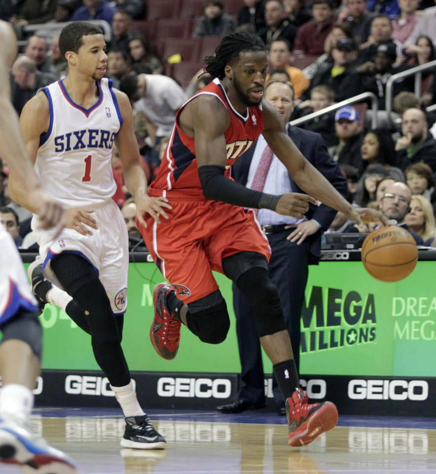 Photo - Atlanta Hawks' DeMarre Carroll, right, moves the ball up court as Philadelphia 76ers' Michael Carter-Williams (1) defends in the first half of an NBA basketball game, Friday, Jan. 31, 2014, in Philadelphia. The Hawks won 125-99. (AP Photo/H. Rumph Jr.)