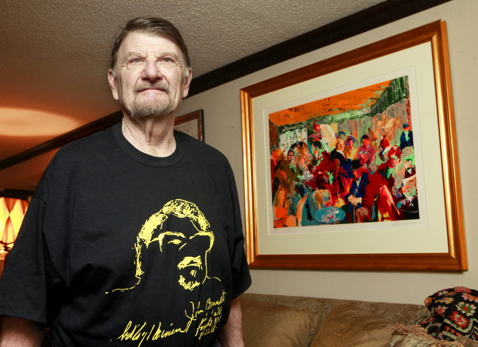 Chef John Bennett with his LeRoy Nieman painting while wearing a T-shirt with the sketch Nieman did of Bennett years ago. <strong>David McDaniel - The Oklahoman</strong>
