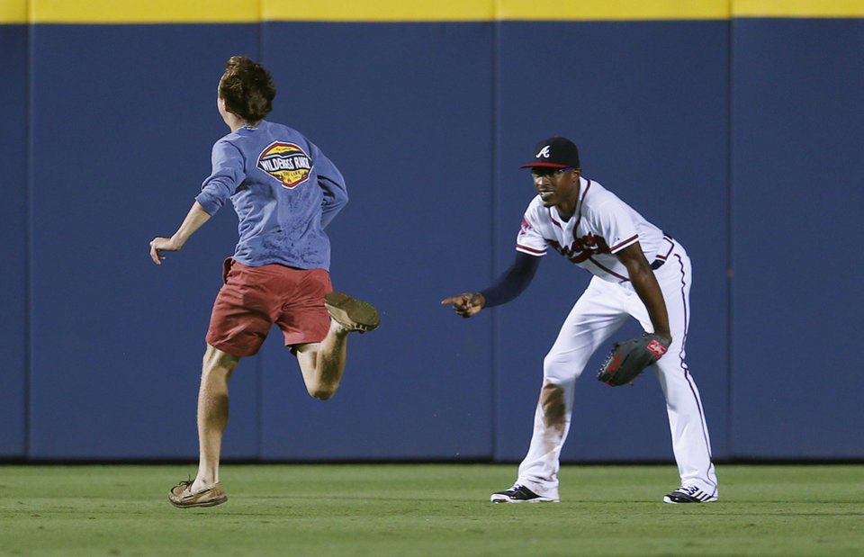 Photo - A spectator who slipped past security and onto the field runs past Atlanta Braves center fielder B.J. Upton  in the ninth inning of the Braves' baseball game against the Philadelphia Phillies in Atlanta, Friday, July 18, 2014. The fan was taken into custody. The the Braves won 6-4. (AP Photo/John Bazemore)