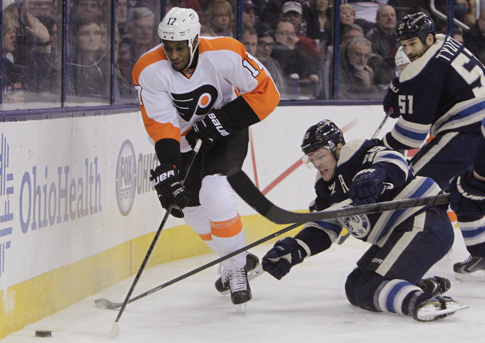 Photo - Philadelphia Flyers' Wayne Simmonds, left, carries the puck past Columbus Blue Jackets' Mark Letestu, center, and Fedor Tyutin, of Russia, during the first period of an NHL hockey game Thursday, Jan. 23, 2014, in Columbus, Ohio. (AP Photo/Jay LaPrete)