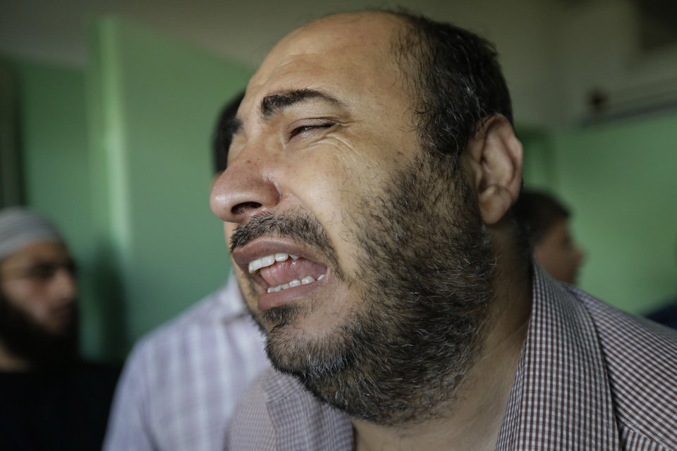 Photo - A Palestinian relative of a person who was wounded in an Israeli strike in Jebaliya refugee camp in the northern Gaza Strip, cries as he exits the emergency room at the Kamal Adwan hospital in Beit Lahiya, Tuesday, July 29, 2014. Israeli Prime Minister Benjamin Netanyahu said Monday that Israel must be ready for a