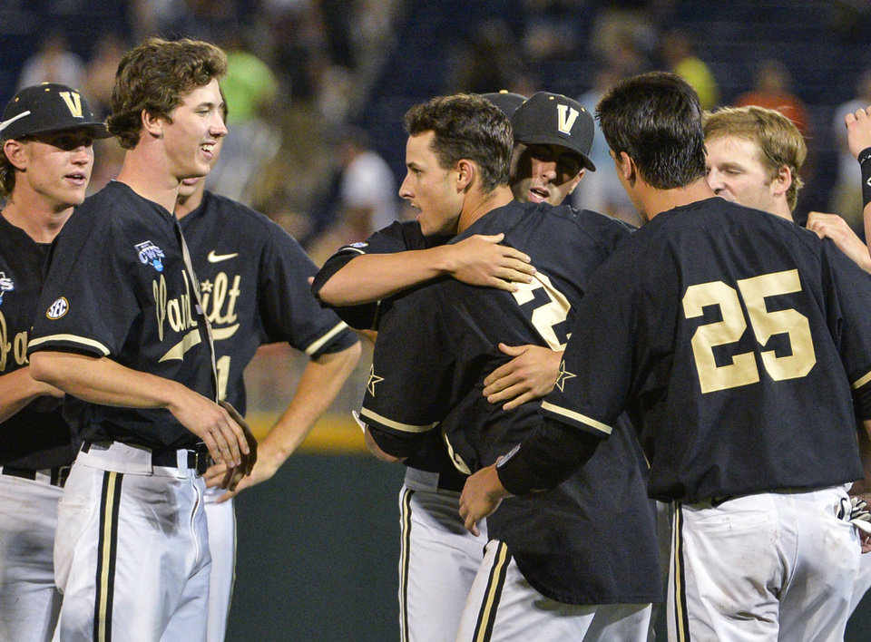 Photo - Vanderbilt players surround Tyler Campbell (2) who hit a single in the 10th inning that scored Rhett Wiseman for a 4-3 win over Texas in an NCAA baseball College World Series game in Omaha, Neb., Saturday, June 21, 2014. Vanderbilt advanced to the championship series. (AP Photo/Ted Kirk)